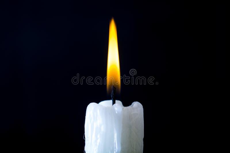 Het witte kaars branden op een zwarte achtergrond stock afbeelding