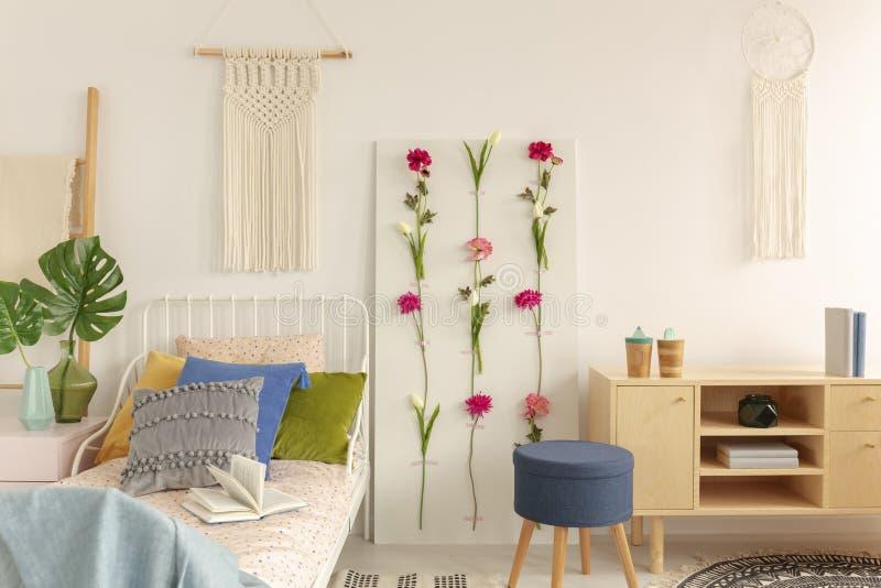 Het witte macramé boven enig metaalbed met kleurrijke hoofdkussens en doted beddegoed in het modieuze binnenland van de bohoslaap royalty-vrije stock foto's