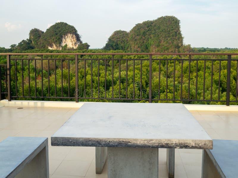 Het witte marmeren bureau en het marmer van de banklijst zitten op dakbovenkant voor met bergheuvel en groene natuurlijke mangrov stock afbeelding