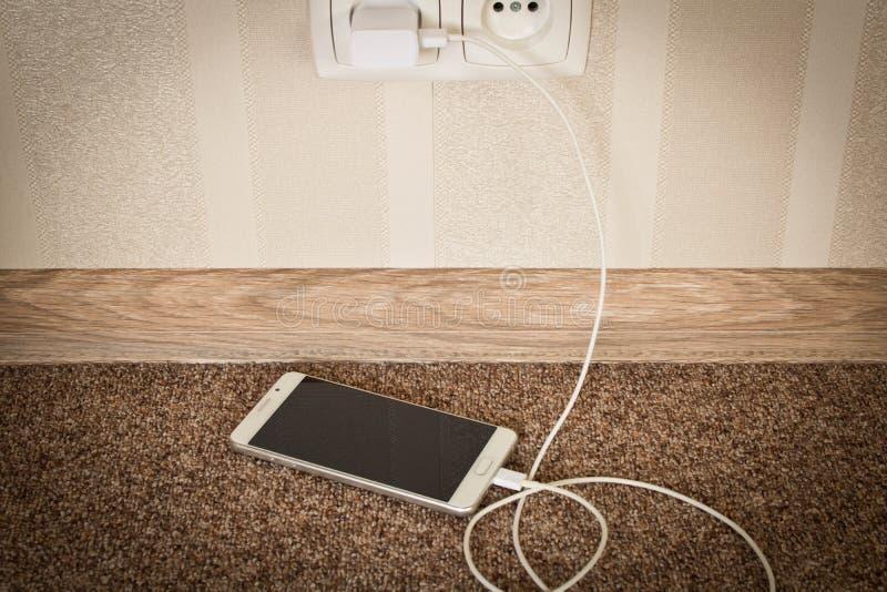 Het witte mobiele telefoon laden Smartphone op last stock afbeelding
