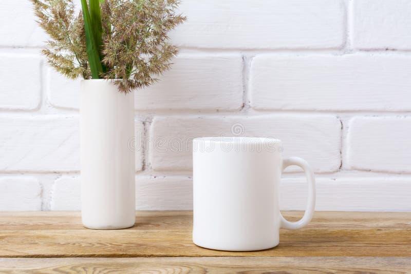 Het witte model van de koffiemok met gras en groene bladeren in cilinder