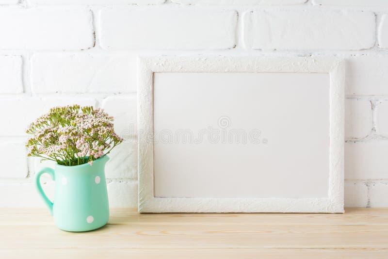 Het witte model van het landschapskader met zachte roze bloemen in waterkruik stock foto