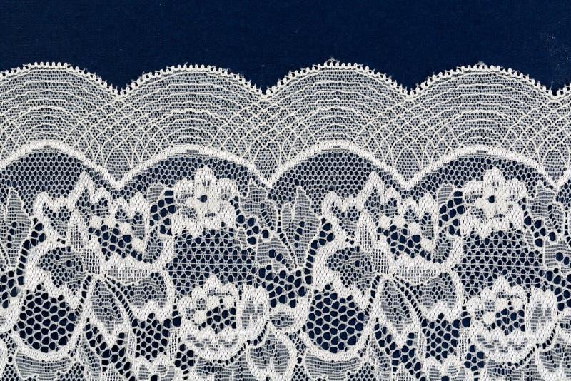 Het witte openwork kant isoleert op blauwe achtergrond stock afbeelding