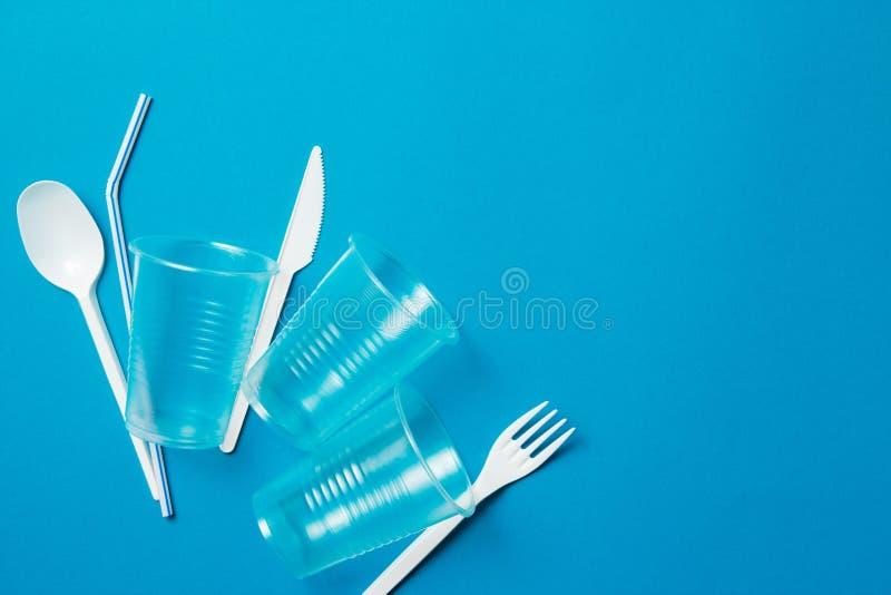 Het witte plastic mes, de lepel, de vork en het plastiek voor ??nmalig gebruik drinken stro op een blauwe achtergrond Zeg nr aan  royalty-vrije stock foto's