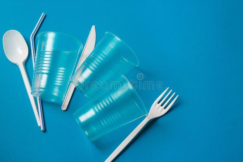 Het witte plastic mes, de lepel, de vork en het plastiek voor ??nmalig gebruik drinken stro op een blauwe achtergrond Zeg nr aan  stock afbeelding
