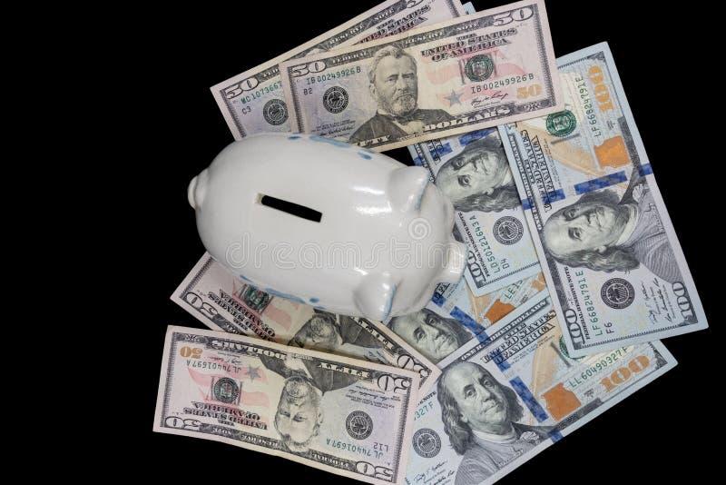 Het witte spaarvarken isoleerde close-up op een stapel van de munt van Verenigde Staten tegen een zwarte achtergrond Rijkdom en b royalty-vrije stock afbeelding