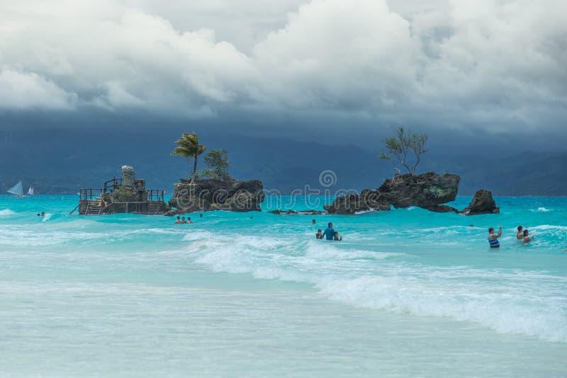 Het witte Strand van Boracay en de mensen zwemmen bij turkooise azuurblauwe Overzees op een bewolkte dag dichtbij Grotwilly's Rot stock foto's