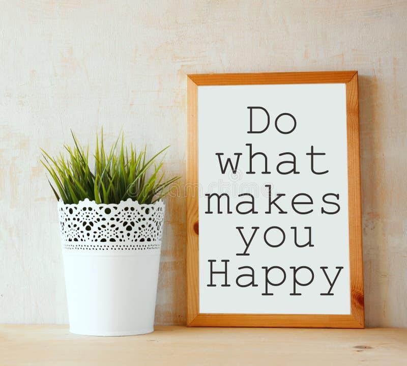 Het witte tekenbord met de uitdrukking doet wat geschreven maakt u gelukkig op het tegen geweven muur is stock afbeeldingen