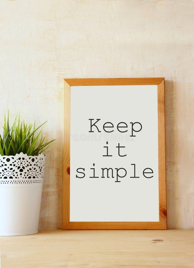 Het witte tekenbord met de uitdrukking houdt het eenvoudig geschreven op het tegen geweven muur royalty-vrije stock afbeelding