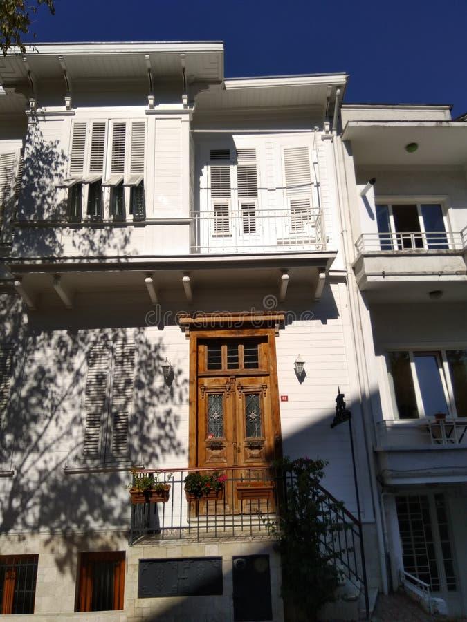Het witte twee vloerherenhuis met houten bruin gaat deur in royalty-vrije stock fotografie