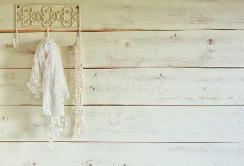 Het witte van het parelshalsband en kant sjaal hangen op houten muur Gefiltreerde wijnoogst Selectieve nadruk royalty-vrije stock afbeelding