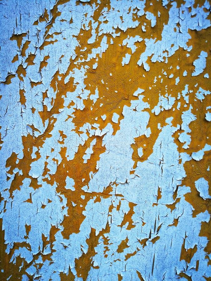 Het witte verf pellen weg op oranje oppervlakte stock afbeelding