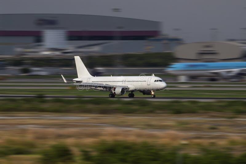 Het witte vliegtuig die op de baan landen royalty-vrije stock fotografie