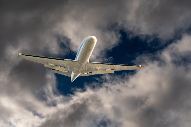Het witte vliegtuig straal vliegen door een gat in donkere gevaarlijke en dramatische onweerswolken royalty-vrije stock foto
