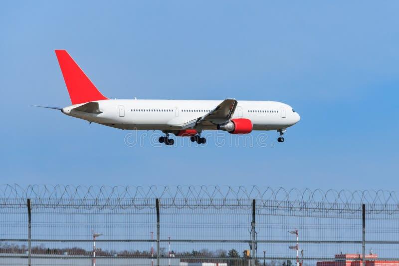 Het witte vliegtuig treft aan het landen over een roosteromheining voorbereidingen royalty-vrije stock foto's