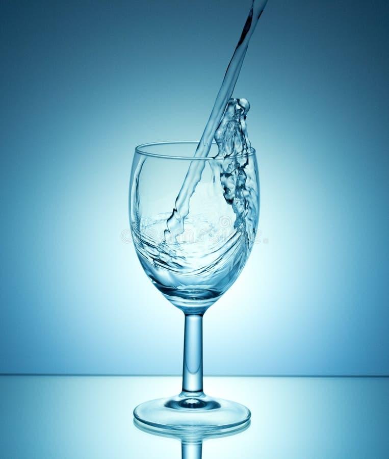 Het witte wijn gieten op blauwe achtergrond royalty-vrije stock afbeelding