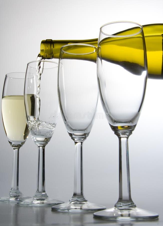 Het witte wijn gieten van fles in wijnglas stock afbeeldingen