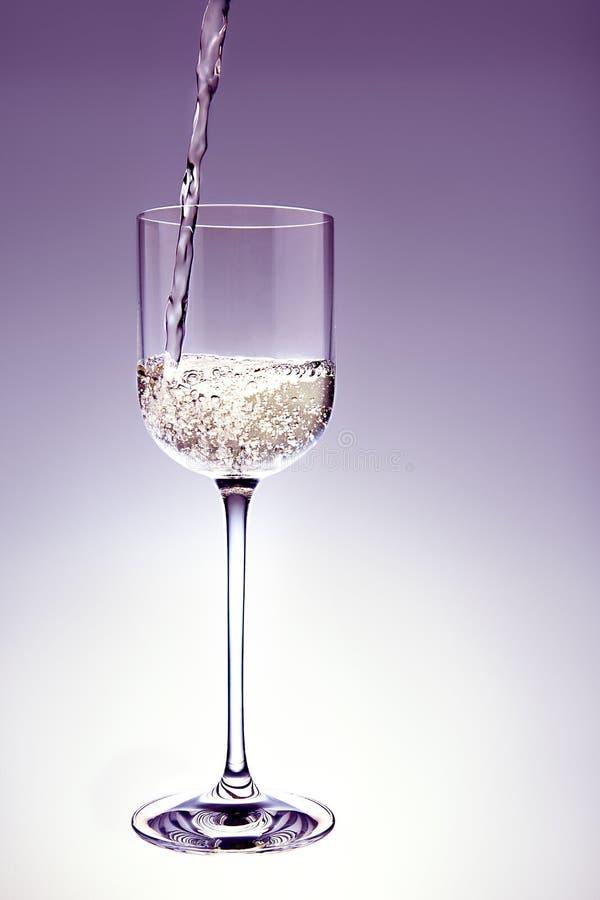 Het witte wijn poring in een kristalglas. stock afbeeldingen