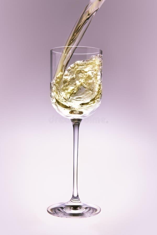 Het witte wijn poring in een kristalglas. royalty-vrije stock fotografie