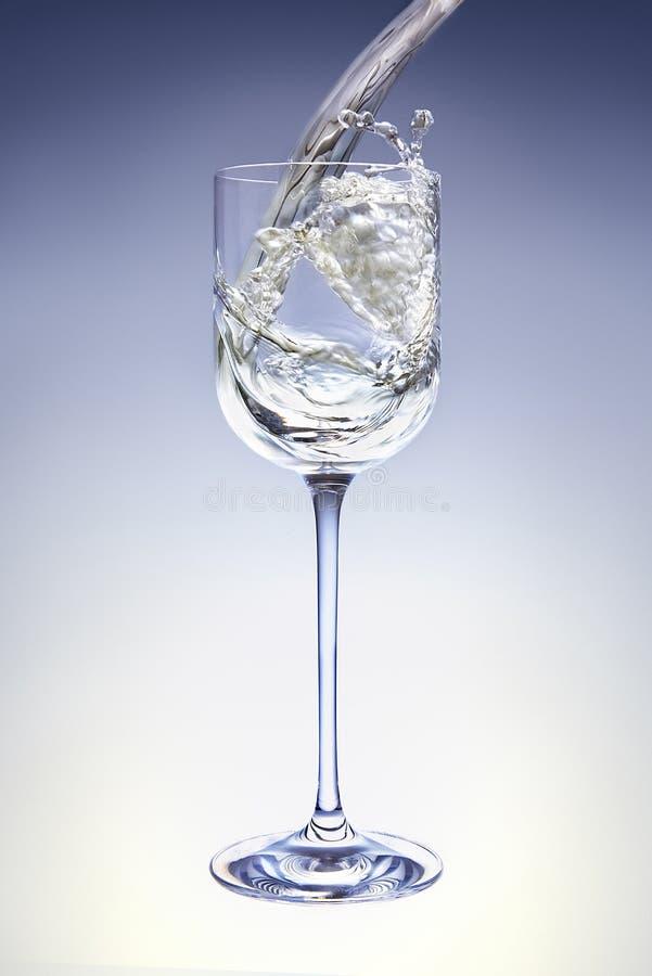 Het witte wijn poring in een kristalglas. stock afbeelding