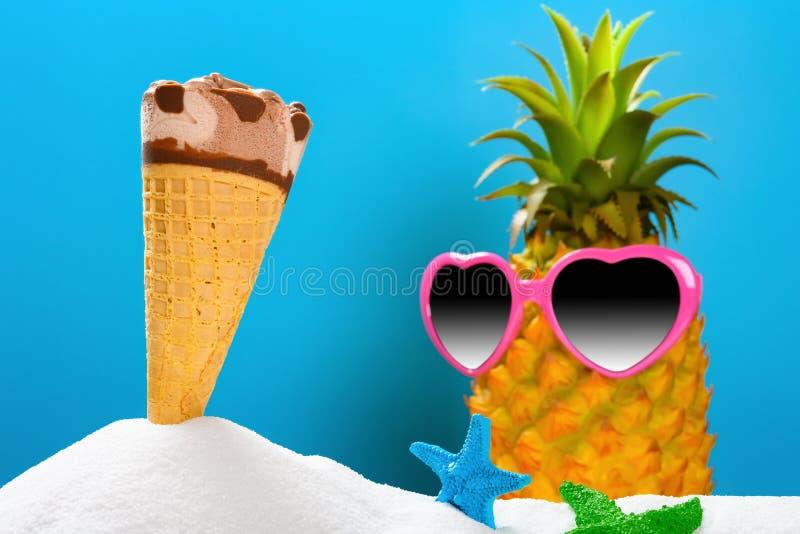 Het witte zand met een roomijskegel & zeesterren en een ananas draagt zonnebrilconcept de zomervakantie stock foto's