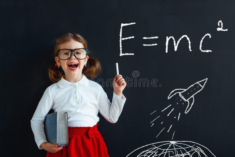 Het wonderstudent van het kindmeisje met boek dichtbij bord royalty-vrije stock afbeeldingen