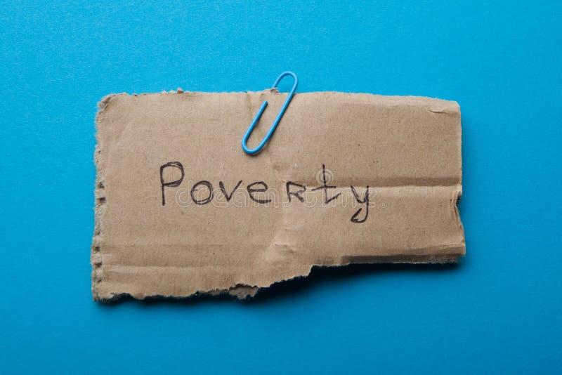 Het woord 'armoede 'op karton wordt, op een blauwe achtergrond, concept wordt geïsoleerd geschreven dat royalty-vrije stock foto