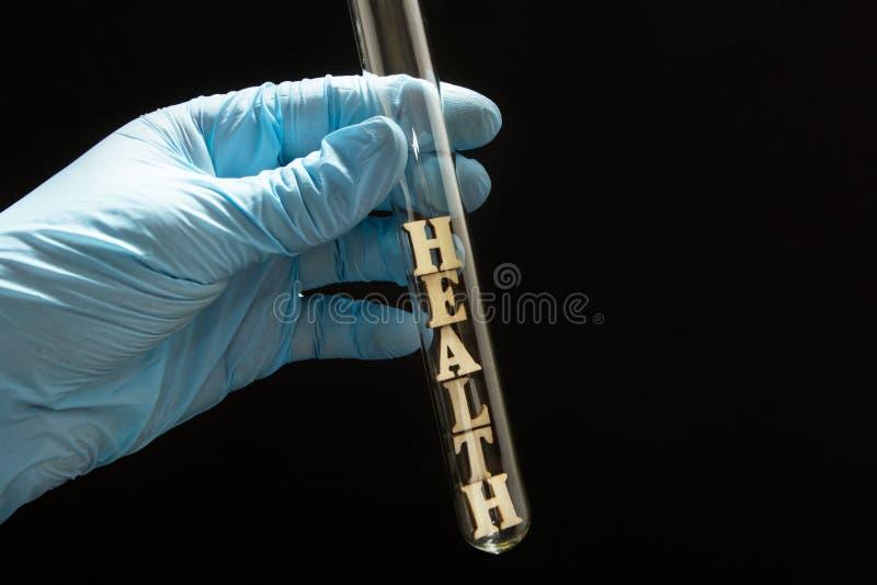 Het woord 'gezondheid 'in een glasreageerbuis is in de handen van een arts in medische handschoenen op een zwarte achtergrond stock fotografie
