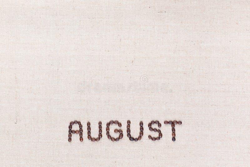Het woord Augustus dat met koffiebonen wordt geschreven hierboven worden geschoten die van, gericht bij de bodem royalty-vrije stock afbeelding