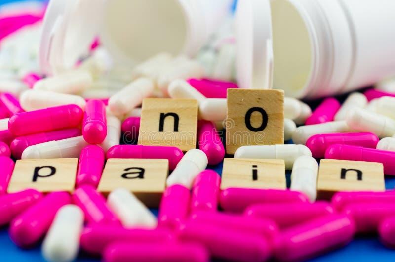 Het woord GEEN PIJN op de achtergrond van verspreide roze en witte capsules en witte kruiken op een blauwe achtergrond stock foto