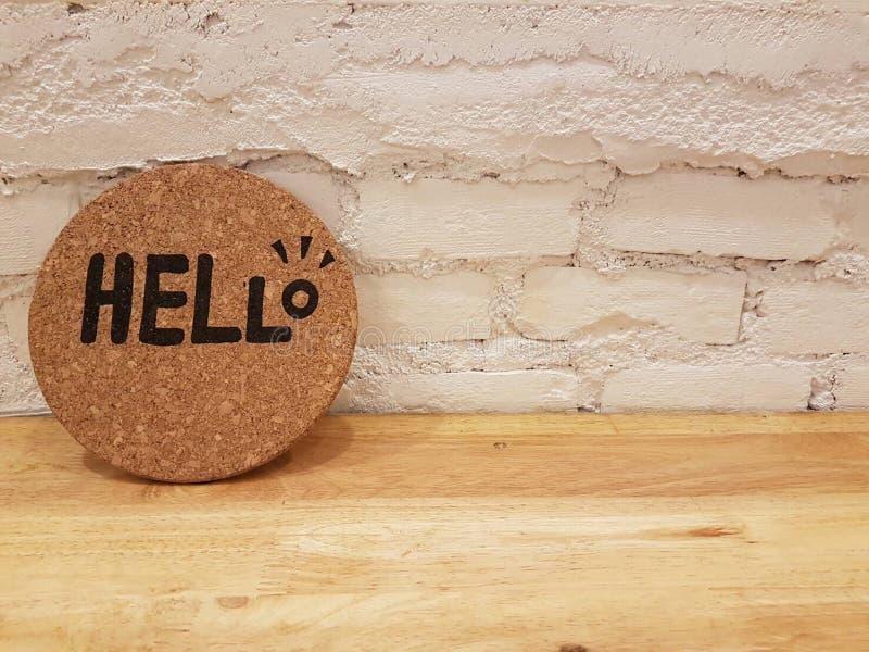 Het woord HELLO op een ronde cork raad wordt geschreven die stock afbeeldingen