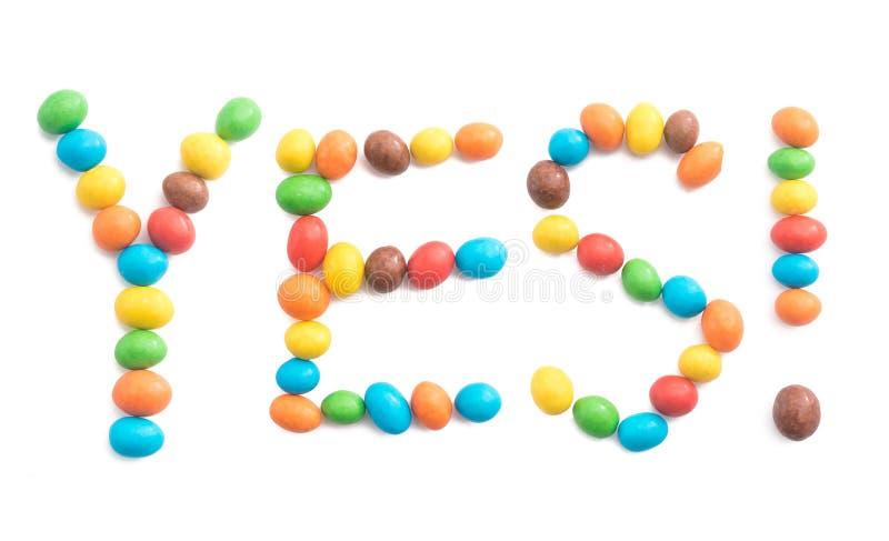Het woord ja uit kleurrijk die suikergoed op witte achtergrond wordt geïsoleerd stock fotografie