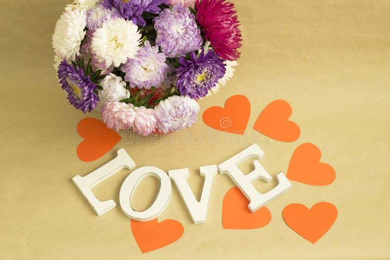 Het woord & x22; love& x22; en een boeket van bloemen op een achtergrond van bruin kraftpapier-document stock fotografie