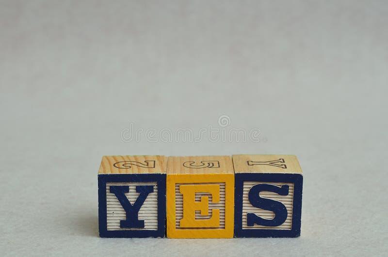 Het woord met kleurrijke alfabetblokken dat ja wordt gespeld stock afbeelding