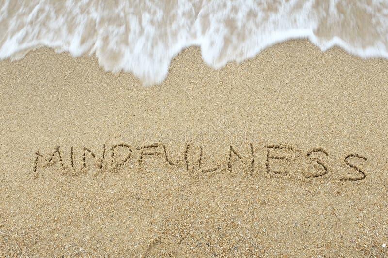 Het woord Mindfulness op zand wordt geschreven dat stock afbeeldingen