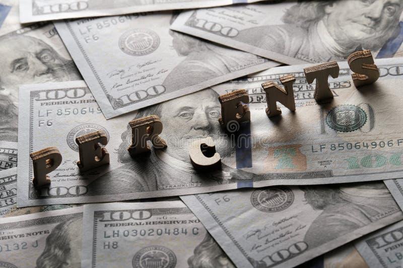 Het woord PERCENTS is gevoerd met houten brieven op de achtergrond van honderd-dollar rekeningen Het concept financiële transacti stock afbeelding
