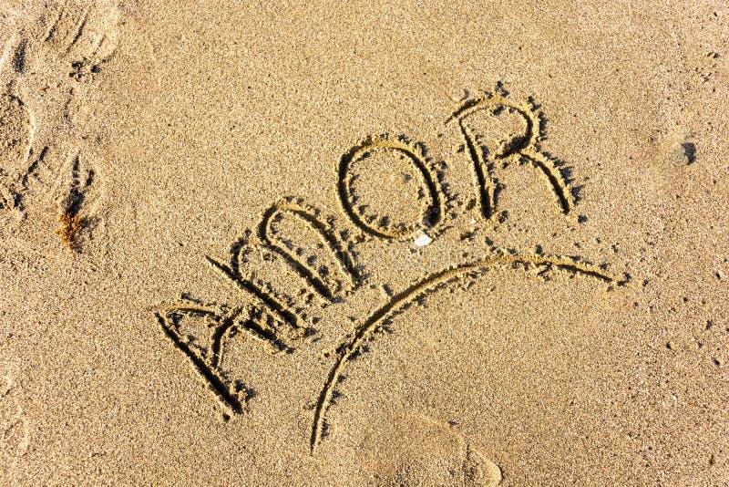 Het woord van de Amorliefde dat in het overzeese zand wordt geschreven royalty-vrije stock fotografie