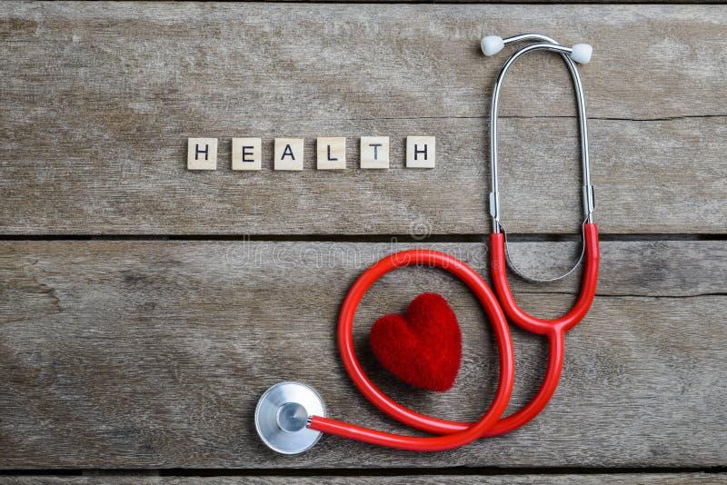 Het woord van de gezondheidstekst met houtsneden en Rood Hart, stethoscoop wordt gemaakt die stock fotografie