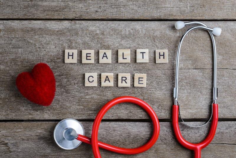 Het woord van de gezondheidszorgtekst met houtsneden en Rood Hart, stethos wordt gemaakt die stock afbeelding