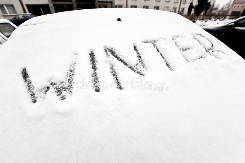 Het woord van de winter op het venster van de auto stock foto's