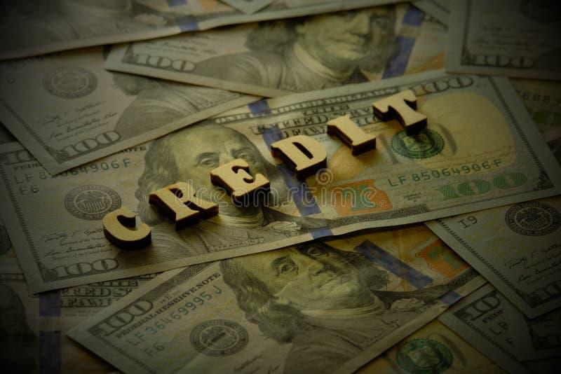 Het woord van houten brieven wordt opgemaakt crediteert op de achtergrond van dollarrekeningen die Het concept een banklening Don stock foto
