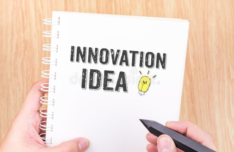 Het woord van het innovatieidee op het witte notitieboekje van het ringsbindmiddel met handhol royalty-vrije stock foto's