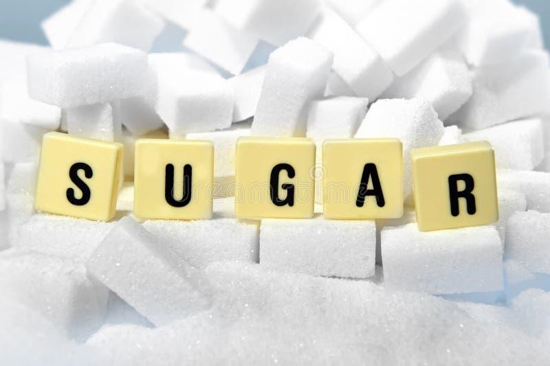 Het woord van suikerblokletters op stapel van suiker kubeert dicht omhoog in verslavingsconcept royalty-vrije stock foto