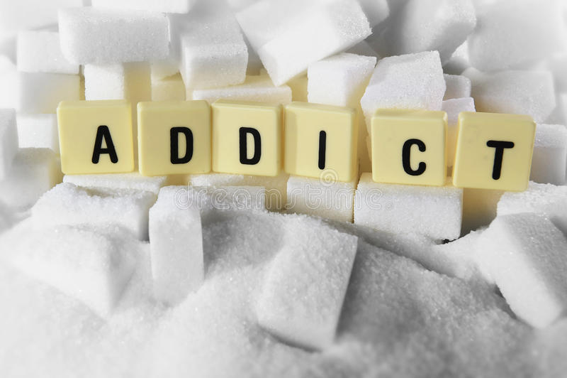 Het woord van verslaafdenblokletters op stapel van suiker kubeert dicht omhoog in het concept van de suikerverslaving stock afbeelding