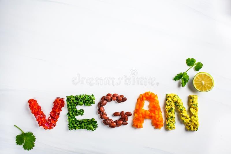 Het woord vegan op witte achtergrond, hoogste mening Vegaans voedselconcept Vegan, samengesteld uit bonen, guacamole, groenten en royalty-vrije stock fotografie