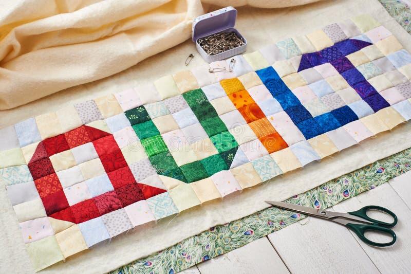 Het woorddekbed van kleurrijke vierkant en driehoeksstukken van stof wordt genaaid die royalty-vrije stock afbeelding