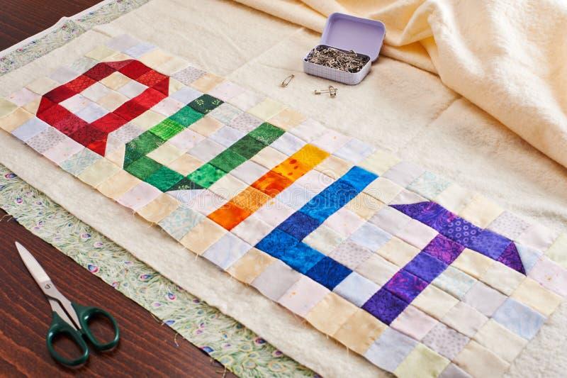Het woorddekbed van kleurrijke vierkant en driehoeksstukken van stof wordt genaaid die stock foto's