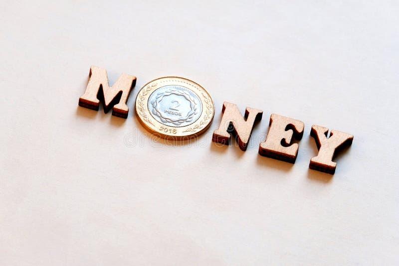Het woordgeld van houten brieven en Argentijns twee-peso muntstuk op een witte achtergrond Cash flow De ruimte van het exemplaar royalty-vrije stock foto