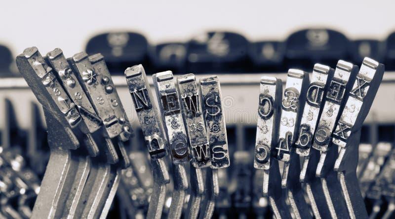 Het woordnieuws met oude typewrterhamers stock fotografie