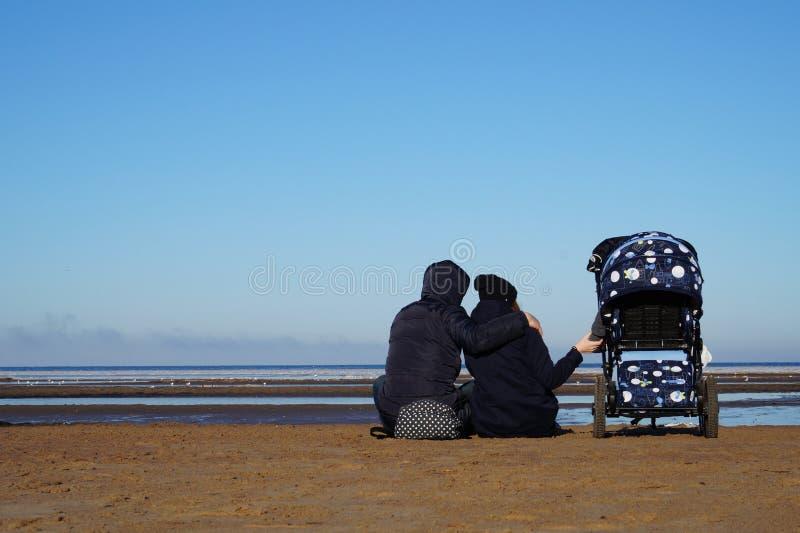 Het zaadpaar met kinderwagen zit op het strand in de lente stock afbeelding